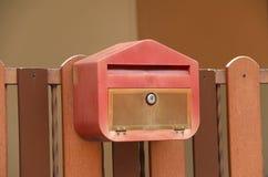 与棕色木篱芭的红色邮箱 免版税库存照片