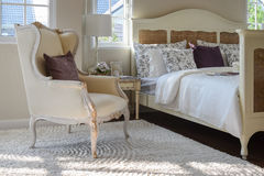 与棕色枕头的经典椅子在地毯在葡萄酒样式卧室 图库摄影