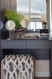 与棕色椅子和辅助部件的黑木梳妆台 免版税库存照片