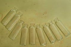 与棕色污点的绿色背景,与以下一个空的玻璃瓶半圈的老纸在右边 免版税库存照片