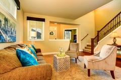 与棕色沙发和两把扶手椅子的米黄家庭娱乐室内部 免版税图库摄影