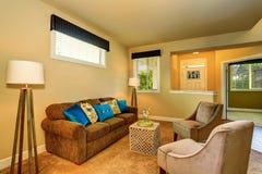 与棕色沙发和两把扶手椅子的米黄家庭娱乐室内部 库存图片