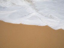 与棕色沙子的白色软的海泡沫波浪层数在海滩在背景的晴天 库存图片