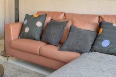 与棕色皮革沙发和黑枕头的现代客厅设计 免版税库存图片
