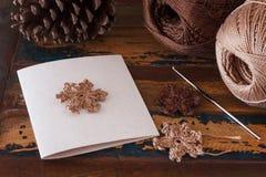 与棕色钩针编织雪花的圣诞节手工制造贺卡 免版税库存图片