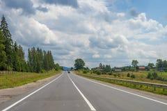 与森林、多云天空和路的夏日风景 免版税库存图片