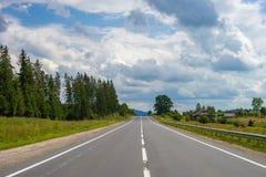 与森林、多云天空和路的夏日风景 免版税图库摄影