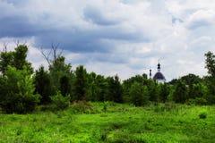 与森林和老教会的夏天俄国国家风景c的 库存照片