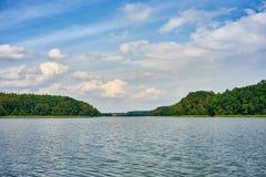 与森林湖的夏天风景在蓝色多云天空下 库存照片