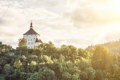 与森林的新的城堡有黄色太阳的发出光线, Banska Stiavnica 免版税库存图片
