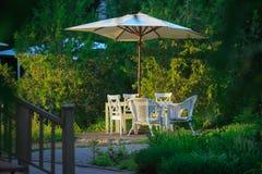 与椅子和舒适的藤条椅子的偏僻的桌在绿色植被中的一个遮光罩下一顿可爱的晚餐的在夏天 免版税库存图片
