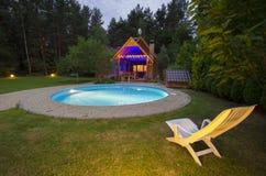 与椅子的一waterpool在木房子附近在晚上 免版税库存图片