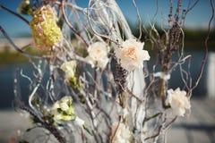 与椅子的婚礼曲拱和许多花和装饰 免版税图库摄影
