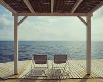 与椅子的暑假背景在海 免版税库存照片
