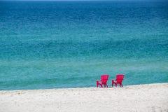 与椅子的白色沙子海滩 免版税库存图片