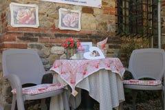 与椅子的装饰桌在石墙背景 Grazzano 免版税图库摄影