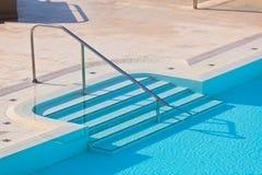 与楼梯的室外游泳池 免版税库存照片