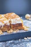 与榛子焦糖顶部的苹果蛋糕 免版税图库摄影