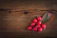 与槭树叶子和红色莓果的秋天木背景 免版税库存照片