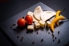与模子、西红柿、蓬蒿和蜜蜂花的乳酪绿化,在一个石盘子的炽热胡椒在深灰背景 免版税库存图片