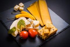 与模子、西红柿、蓬蒿和蜜蜂花的乳酪绿化,在一个石盘子的炽热胡椒在深灰背景 免版税图库摄影