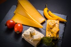 与模子、西红柿、蓬蒿和蜜蜂花的乳酪绿化,在一个石盘子的炽热胡椒在深灰背景 库存图片