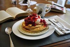 与樱桃顶部的早餐薄煎饼在桌上 免版税库存照片