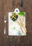 与橄榄、蓬蒿、迷迭香和面包切片的新鲜的希腊白软干酪在白色陶瓷服务上在土气木 库存图片