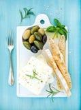 与橄榄、蓬蒿、迷迭香和面包切片的新鲜的希腊白软干酪在白色陶瓷服务上在明亮的绿松石 库存照片