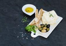 与橄榄、蓬蒿、迷迭香和面包切片的新鲜的希腊白软干酪在白色陶瓷服务上在黑板岩石头 库存图片