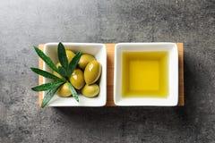 与橄榄油和成熟橄榄的盘在桌上 免版税库存照片