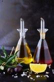 与橄榄油和葡萄酒醋玻璃瓶子的灰色抽象背景用柠檬、海盐、大蒜和橄榄树枝 空间 免版税库存图片