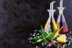 与橄榄油和葡萄酒醋玻璃瓶子的灰色抽象背景用柠檬、海盐、大蒜和橄榄树枝 空间 免版税库存照片