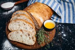 与橄榄油的切的自创意大利ciabatta面包在黑暗的背景 Ciabatta,草本,橄榄油,面粉 关闭看法,复制s 免版税图库摄影