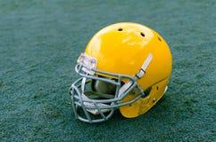 与橄榄球盔的体育场草对此 免版税库存图片