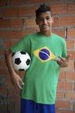 与橄榄球足球的微笑的巴西青少年的立场 免版税库存照片