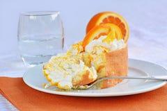 与橙色切片和打好的奶油的乳酪蛋糕卷 库存图片