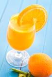 与橙色切片的新鲜的橙汁在蓝色木背景,桔子,芒果,饮料,健康lif的产品摄影的玻璃 库存图片