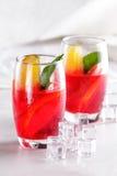 与橙色切片的新鲜水果拳打和茶点的冰块 库存图片