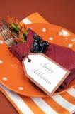 与橙色圆点和条纹板材和餐巾-垂直的愉快的万圣夜桌餐位餐具。 库存图片
