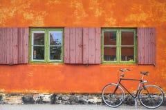 与橙色墙壁和葡萄酒自行车的Windows 免版税库存照片
