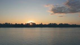 与橙色天空和桃红色云彩的美好的日落在河上 股票录像