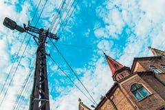 与橙色屋顶和电子杆和导线,底视图的古色古香的红砖老大厦,被定调子 免版税库存图片