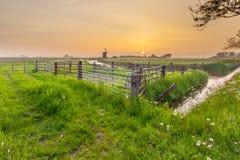 与橙色日落的开拓地风景在格罗宁根,荷兰 免版税图库摄影