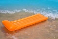 与橙色浮动的休息室和通知的海滩岸 免版税图库摄影