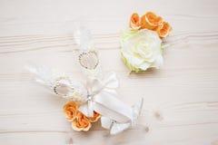与橙色玫瑰和白花的两块婚姻的玻璃 免版税库存照片