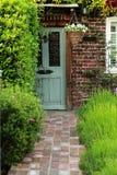 与橙色砖墙壁和绿色淡紫色庭院的灰色老门 库存照片