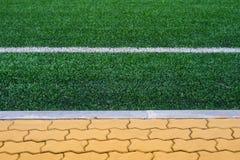 与橙色砖平台的足球场草 库存图片