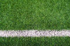 与橙色砖平台的足球场草 免版税库存图片