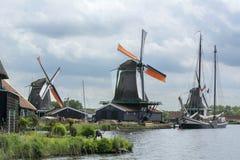 与橙色翼的三个荷兰磨房在有一条美丽的小船的运河附近在多云天空下 图库摄影